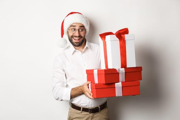 Buon natale, concetto di vacanze. uomo emozionante che celebra il natale, indossa il cappello della santa e tiene i regali, in piedi