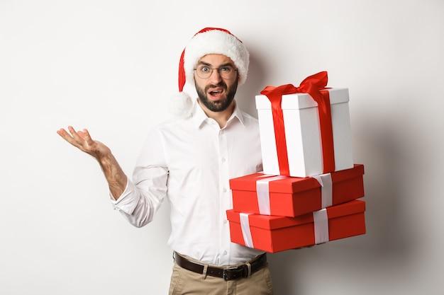 Buon natale, concetto di vacanze. uomo che guarda confuso mentre tiene i regali di natale, scrollando le spalle perplesso, in piedi in santa cappello su sfondo bianco.
