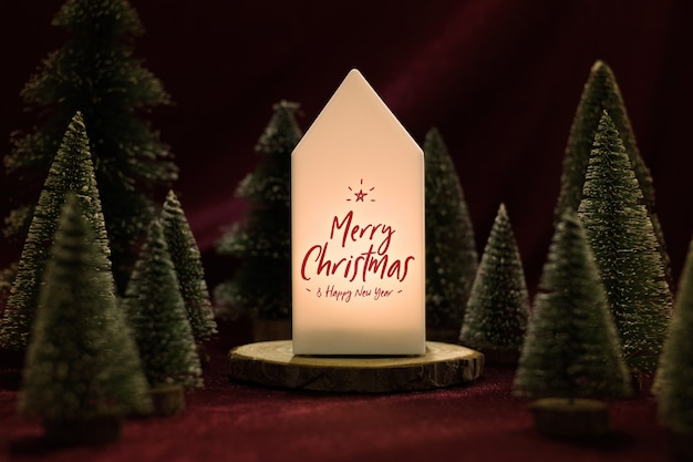 Merry christmas on home lamp with xmas tree on velvet fabric table in dark night
