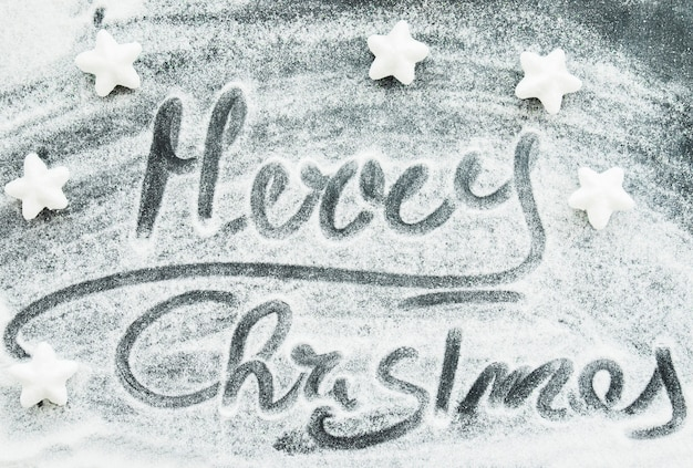 Merry christmas inscription between decorative snow and stars