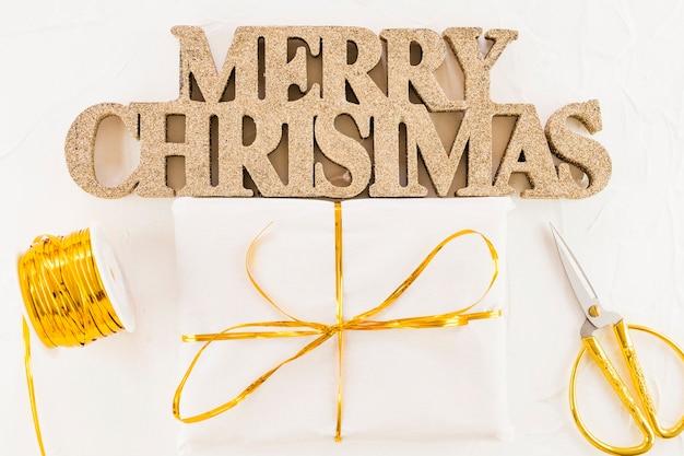 Merry christmas inscription near present box, scissors and ribbon