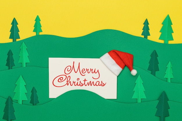 Merry christmas lettering on greeting card with forest trees landscape in paper cut style.