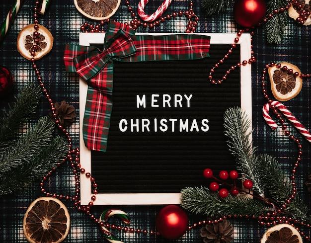 Счастливого рождества надписи пластиковыми буквами на доске для писем. вокруг карамельные тростники, шары, шишки, еловые ветки и сушеный апельсин. вид сверху. рождественская открытка.