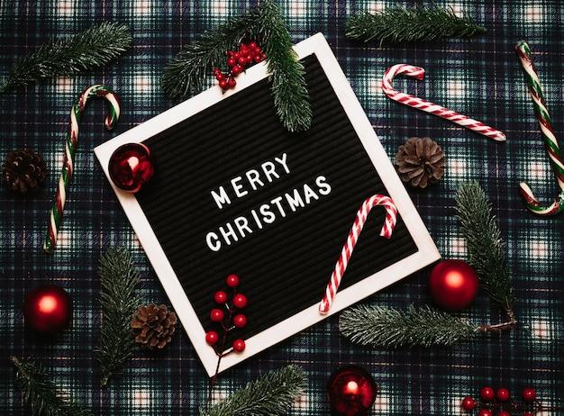 Счастливого рождества надписи пластиковыми буквами на старой винтажной доске для писем. на заднем плане - карамельные трости, шары, шишки и еловые ветки. вид сверху. флэтли. рождественская открытка.