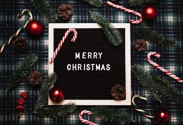 Счастливого рождества надписи пластиковыми буквами на старой винтажной доске для писем. вокруг карамельные трости, шары, шишки и еловые ветки. вид сверху. флэтли. готовая рождественская открытка.