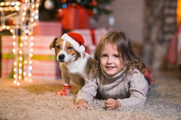 Счастливого рождества. маленькая девочка дома у камина с собакой джек рассел терьер и новогодняя елка с подарками и светящимися гирляндами празднует рождество