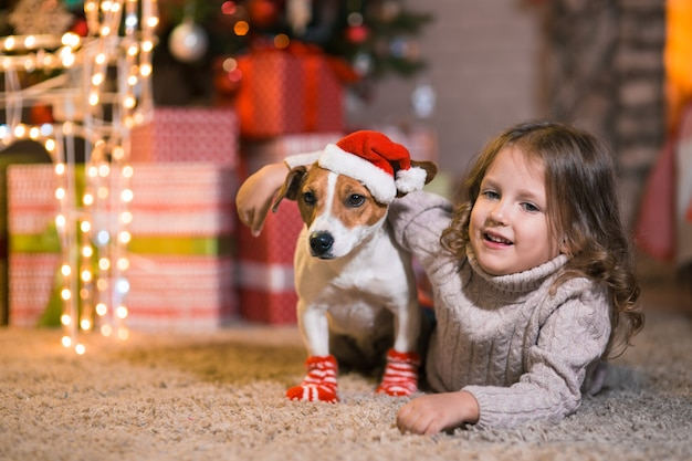 Счастливого рождества. маленькая девочка дома у камина с собакой джек рассел терьер в красно-белых носках и новогодней елкой с подарками и светящимися гирляндами празднует рождество