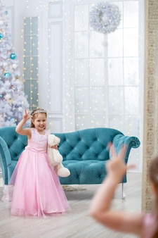 Merry christmas! little girl in fancy dress poses in front of a large mirror