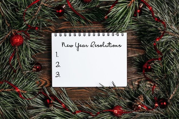 Merry christmas and merry new year concept with gift boxes, toys and notebook with text new year resolutions
