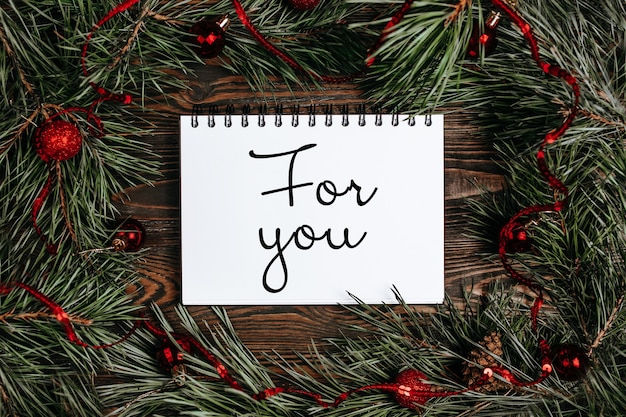 Merry christmas and merry new year concept with gift boxes, toys and notebook with text