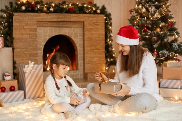 메리 크리스마스! 집에서 선물을 가진 엄마와 아이가 소녀