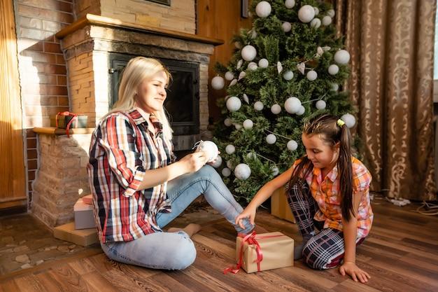 Счастливого рождества. мать и дочь ребенка девочка обмениваются рождественскими подарками