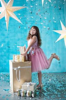 メリークリスマス!新年2020!女の子が贈り物の近くに立っています。彼女の誕生日の女の子のための予想外の驚き。小さな女の子を大きな笑顔で祝うと紙吹雪が投げられます。贈り物に喜んでいる女の子
