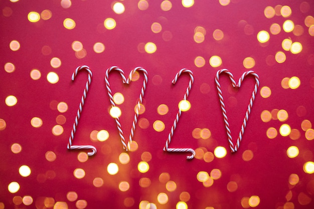Merry christmas and new year 2020 composition with striped candy canes in the shape of a heart with light on a red background.