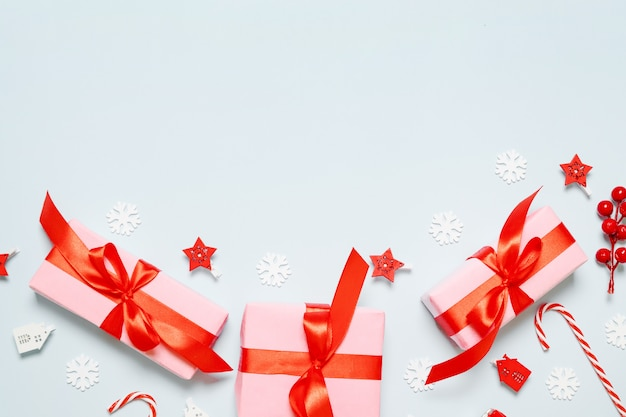 Merry christmas and new year congratulation card with pink paper boxes, red ribbons, glitter, stars on blue background