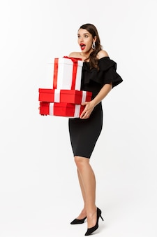 Buon natale e anno nuovo concetto di vacanze. donna emozionante e felice in vestito nero che tiene i regali di natale, guardando sorpreso dal logo. in piedi con regali su sfondo bianco.
