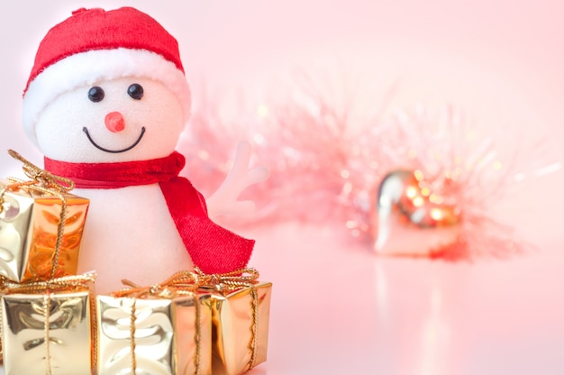 Merry christmas, new year, snowman gifts in golden boxes and a golden heart on a background of pink and yellow bokeh.