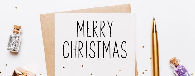 白い背景に封筒、ギフト、ゴールドのキラキラ星とメリークリスマスノート。メリークリスマスと新年のコンセプト