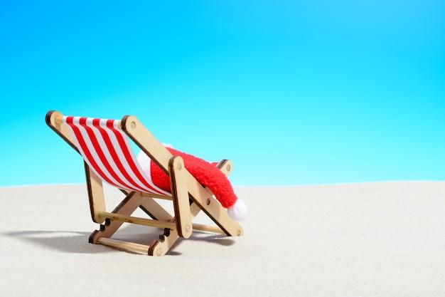 해변 개념에 메리 크리스마스입니다. 산타 모자와 라운지 의자