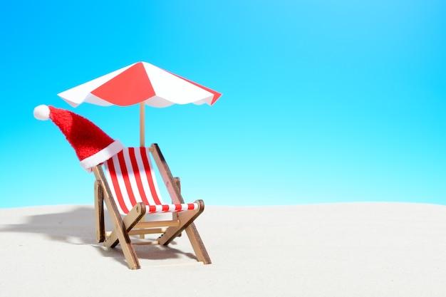 해변 개념에 메리 크리스마스입니다. 우산과 산타 모자가있는 라운지 의자