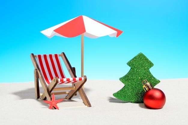 해변 개념에 메리 크리스마스입니다. 우산과 크리스마스 장식이있는 라운지 의자