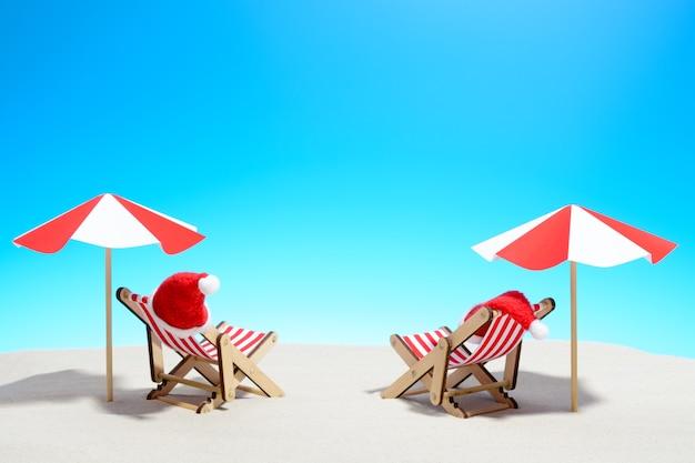 해변 개념에 메리 크리스마스입니다. 우산과 산타 모자가있는 라운지 의자 2 개