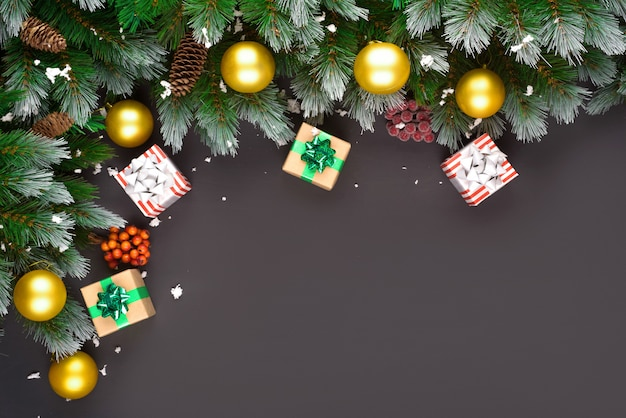 Счастливого рождества или счастливого нового года кадр композиции. еловые ветки, елочные игрушки, подарочная коробка, пушистый снег, сосновые шишки, конфеты и зимние ягоды на черном фоне. плоская планировка, скопируйте пространство для вашего текста.