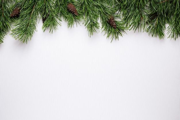 松の枝の境界線とメリークリスマスまたは新年の白い背景