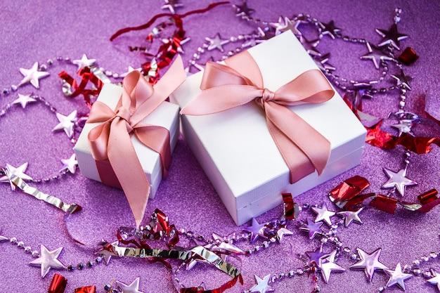 С рождеством или днем святого валентина открытка из украшений из белых подарочных коробок с лонжероном из розовой ленты ...