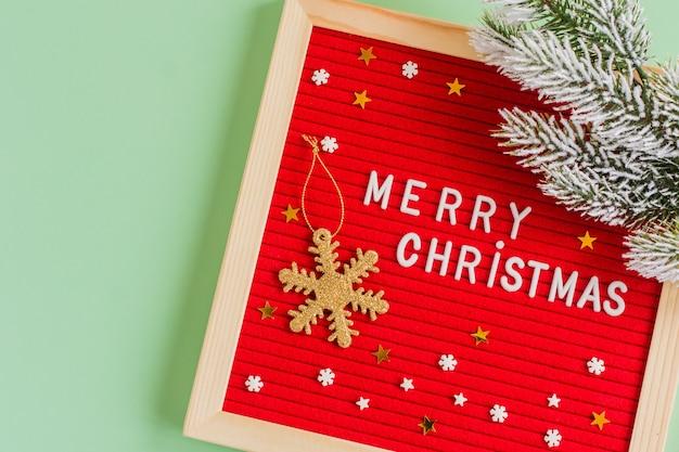 緑の背景に金の雪の偽物とモミの木の枝で飾られたメリークリスマスの引用。