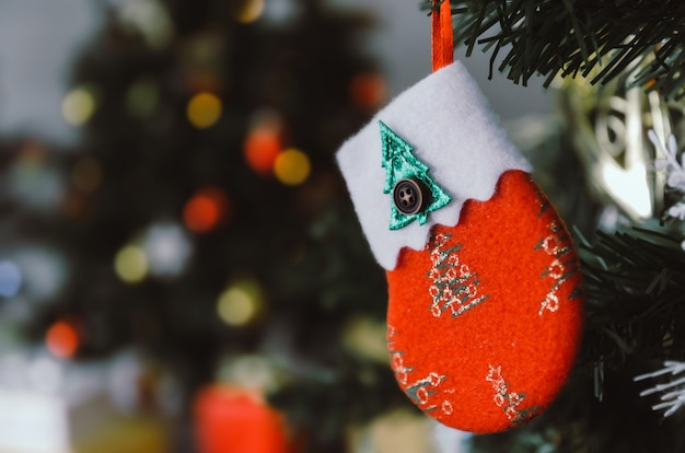 Merry christmas. red color decorated sock hanging on christmas tree, holiday family, happy new year and merry christmas festival concept, vintage color tone effect