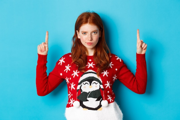 Merry christmas. serious and suspicious redhead girl staring at camera, pointing fingers up at promo offer, standing in xmas sweater against blue background.