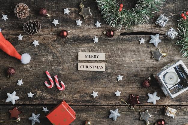 休日の装飾で囲まれた素朴な木製の机の上のメリークリスマスのサイン