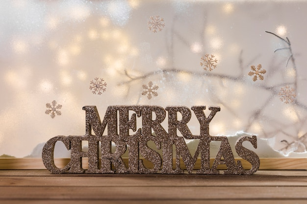 Merry christmas sign on wood table near bank of snow, snowflakes and fairy lights