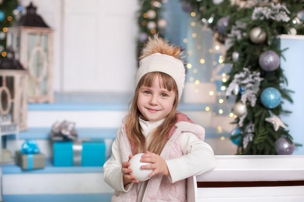 Счастливого рождества! поверхность. маленькая девочка в шляпе со снегом в руках возле почтового ящика в зимнем дворе. девушка отправила письмо деду морозу со списком рождественских подарков. ребенок отправляет сообщение на северный полюс.