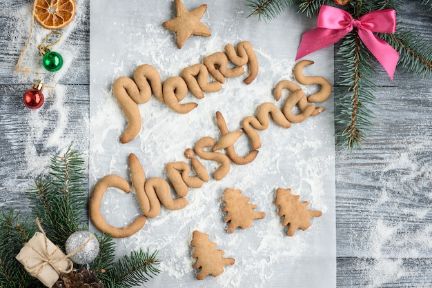 Merry christmas text of homemade gingerbread. christmas composition of fir branches, cone, bow, balls and gingerbread cookies on grey wooden board.