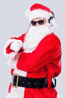С рождеством тебя! санта-клаус в солнцезащитных очках и наушниках, указывая на вас, стоя на сером фоне