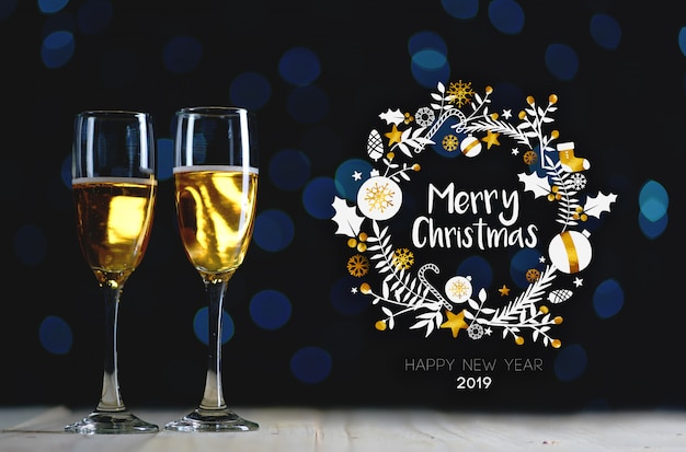 Merry christmas typography art. two glasses of champagne dark glow lights background