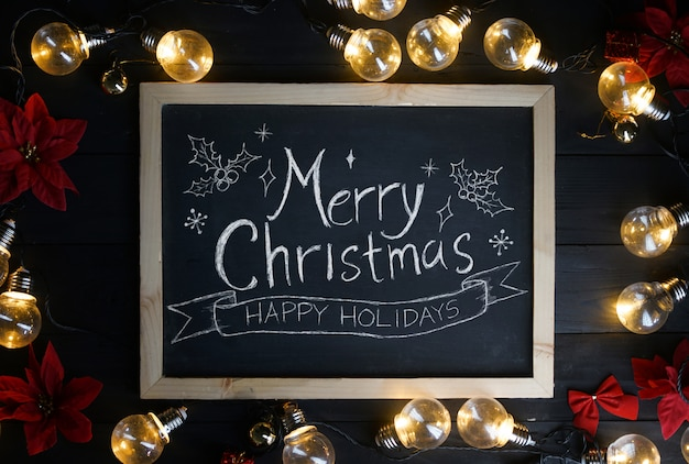 Merry christmas typography on blackboard between light bulbs and red poinsettia on black wood
