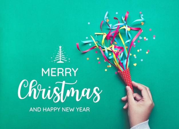 화려한 색종이 조각, 깃발을 들고 손으로 메리 크리스마스. 평면 배치 디자인