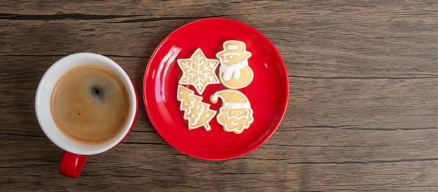 木製のテーブルの背景に自家製クッキーとコーヒーカップとメリークリスマス。クリスマスイブ、パーティー、休日、新年あけましておめでとうございますのコンセプト