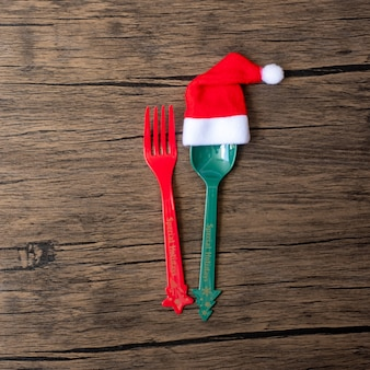 Merry christmas with miniature santa claus, fork and spoon on wood table background. xmas, party and happy new year concept