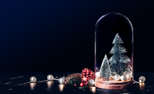 Merry christmas with mistletoe with xmas tree and glowing light string and pine cone on marble table