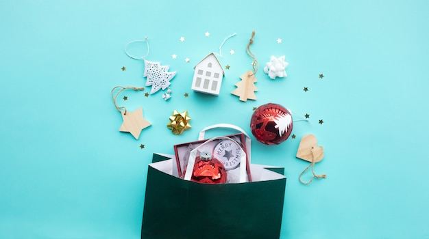Merry christmas with ornament prop element and shopping bag on color background.