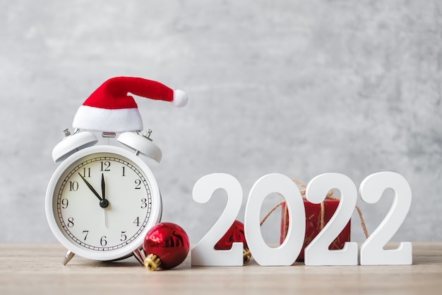 木製のテーブルにヴィンテージの目覚まし時計と2022年の番号とメリークリスマス。明けましておめでとう、パーティー、休日、ボクシングデーのコンセプト