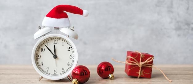木製のテーブルにヴィンテージの目覚まし時計とクリスマスの装飾が施されたメリークリスマス。パーティー、休日、ボクシングデーのコンセプト