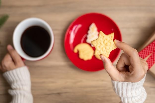 테이블에 커피 컵과 집에서 만든 쿠키를 들고 여자 손으로 메리 크리스마스. 크리스마스 이브, 파티, 휴일 및 새해 복 많이 받으세요 개념