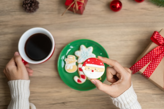 Merry christmas with woman hand holding coffee cup and homemade cookie on table. xmas eve, party, holiday and happy new year concept