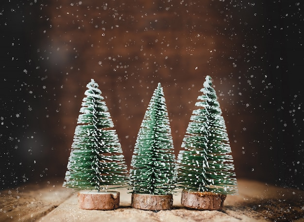 Merry christmas with xmas tree and snow falling on wood table