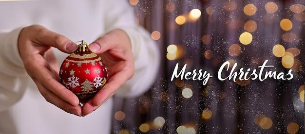 雪とボケとクリスマスの赤いボールきらめきの背景を保持しているメリークリスマスの女性の手